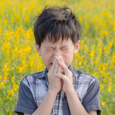 little boy blowing nose in flower field